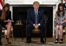 "FILE - In this Feb. 21, 2018, file photo, President Donald Trump, joined by student Carson Abt, right, and Julia Cordover, the student body president at Marjory Stoneman Douglas High School in Parkland, Fla., left, bow their heads during the opening prayer of a listening session with high school students and teachers in the State Dining Room of the White House in Washington. When shots rang out at a high school in Parkland, Florida last year, leaving 17 people dead, Trump quickly turned his thoughts to the need for more mental institutions. When back-to-back mass shootings in Dayton, Ohio, and El Paso, Texas, jolted the nation earlier this month, Trump again raised the need for ""building new facilities"" for the mentally ill as a way to prevent mass shootings. (AP Photo/Carolyn Kaster, File)"