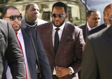 FILE - In this June 26, 2019, file photo, R&B singer R. Kelly, center, arrives at the Leighton Criminal Court building for an arraignment on sex-related felonies in Chicago. R. Kelly pleaded not guilty Friday, Aug. 2, 2019, in New York, to federal charges he sexually abused women and girls. The 52-year-old Kelly was denied bail in a Brooklyn courtroom packed with his supporters. (AP Photo/Amr Alfiky, File)