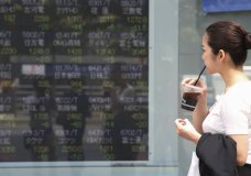 A woman looks at an electronic stock board of a securities firm in Tokyo, Monday, Sept. 2, 2019. Asian stock markets are mixed after Washington and Beijing stepped up their trade war with a new round of tariff hikes. (AP Photo/Koji Sasahara)