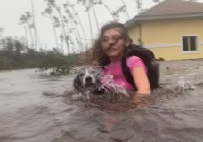 ulia Aylen wades through waist deep water carrying her pet dog as she is rescued from her flooded home during Hurricane Dorian in Freeport, Bahamas, Tuesday, Sept. 3, 2019. Practically parking over the Bahamas for a day and a half, Dorian pounded away at the islands Tuesday in a watery onslaught that devastated thousands of homes, trapped people in attics and crippled hospitals. (AP Photo/Tim Aylen)
