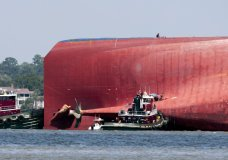 Rescuers work near the stern of the vessel Golden Ray as it lays on its side near the Moran tug boat Dorothy Moran, Monday, Sept. 9, 2019, in Jekyll Island, Ga. Coast Guard rescuers have made contact with four South Korean crew members trapped inside the massive cargo ship off the coast of Georgia. (AP Photo/Stephen B. Morton)