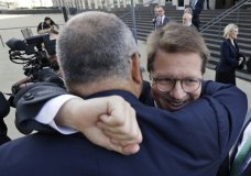 Attorney Mark Lanier gets a hug outside the U.S. Federal courthouse, Monday, Oct. 21, 2019, in Cleveland. The nation's three dominant drug distributors and a big drugmaker have reached a $260 million deal to settle a lawsuit related to the opioid crisis just as the first federal trial over the crisis was due to begin Monday. (AP Photo/Tony Dejak)