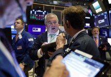 Edward McCarthy, center, works with fellow traders on the floor of the New York Stock Exchange, Tuesday, Oct. 29, 2019. Stocks are off to a slightly lower start on Wall Street as communications and energy companies fall. (AP Photo/Richard Drew)