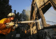 Firefighters work on a house destroyed by a wildfire called the Getty Fire in Los Angeles, Monday, Oct. 28, 2019. (AP Photo/Ringo H.W. Chiu)