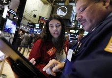 FILE - In this Oct. 7, 2019, file photo traders Ashley Lara and John Santiago confer as they work on the floor of the New York Stock Exchange. The U.S. stock market opens at 9:30 a.m. EDT on Wednesday, Oct. 16. (AP Photo/Richard Drew, File)