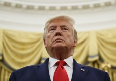 President Donald Trump stands during a Presidential Medal of Freedom ceremony for auto racing great Roger Penske in the Oval Office of the White House, Thursday, Oct. 24, 2019, in Washington. (AP Photo/Alex Brandon)