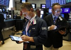 FILE - In this Oct. 7, 2019, file photo trader Robert Charmak, left, works on the floor of the New York Stock Exchange. The U.S. stock market opens at 9:30 a.m. EDT on Tuesday, Oct. 29. (AP Photo/Richard Drew, File)
