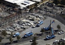 FILE - In this Oct. 14, 2017, file photo, Pacific Gas & Electric Co. crews work on restoring power lines in a fire ravaged neighborhood in an aerial view in the aftermath of a wildfire in Santa Rosa, Calif. PG&E says it will begin turning off power to 800,000 customers in 34 counties starting after midnight Wednesday, Oct. 9, 2019. (AP Photo/Marcio Jose Sanchez, File)