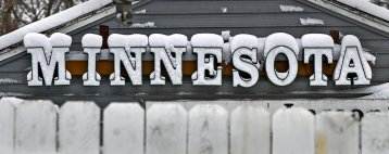 Fresh snow covers a sign Wednesday, Nov. 27, 2019, in St. Cloud, Minn. According to the National Weather Service, St. Cloud received four inches of snow overnight. (Dave Schwarz/The St. Cloud Times via AP)