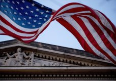 FILE - In this March 22, 2019 file photo, an American flag flies outside the Department of Justice in Washington. A federal appeals panel is voicing skepticism over the Justice Department's claim that it can defy Congress' request for secret material from the Mueller report. Two of the three judges who heard arguments at a hearing Tuesday seemed prepared to order at least some of the material sought by the House for its impeachment inquiry to be turned over. (AP Photo/Andrew Harnik)