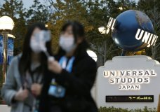 Visitors pose for a selfie in front of Universal Studios Japan in Osaka, western Japan Friday, Feb. 28, 2020. The theme park on Friday announced its temporary closure to prevent the spread of a new coronavirus. (Kyodo News via AP)