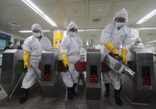 Workers wearing protective gears spray disinfectant as a precaution against the new coronavirus at a subway station in Seoul, South Korea, Friday, Feb. 28, 2020. Japan's schools prepared to close for almost a month and entertainers, topped by K-pop superstars BTS, canceled events as a virus epidemic extended its spread through Asia into Europe and on Friday, into sub-Saharan Africa. (AP Photo/Ahn Young-joon)