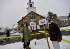 Richard Mellon and Tom Duston hold up signs for Democratic presidential candidate Sen. Elizabeth Warren, D-Mass., outside the Chesterfield, N.H., Town Hall during the New Hampshire presidential primary elections, Tuesday, Feb. 11, 2020. (Kristopher Radder/The Brattleboro Reformer via AP)