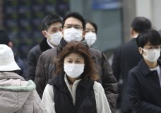 People wearing protective face masks cross a street in Tokyo, Monday, Feb. 17, 2020. Chinese authorities on Monday reported a slight upturn in new virus cases and hundred more deaths for a total of thousands since the outbreak began two months ago. (AP Photo/Koji Sasahara)