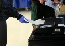 In this Saturday, March 14, 2020 photo, voters cast their ballots during early voting in Chicago while wearing protective gloves. Residents and poll workers took extra precautions amid concerns over the coronavirus. The Illinois state primary elections are scheduled for Tuesday, March 17. (AP Photo/Noreen Nasir)