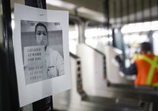 """A flier urging customers to remain home hangs at a turnstile as an MTA employee sanitizes surfaces at a subway station with bleach solutions due to COVID-19 concerns, Friday, March 20, 2020, in New York. New York Gov. Andrew Cuomo is ordering all workers in non-essential businesses to stay home and banning gatherings statewide. """"Only essential businesses can have workers commuting to the job or on the job,"""" Cuomo said of an executive order he will sign Friday. Nonessential gatherings of individuals of any size or for any reason are canceled or postponed. (AP Photo/John Minchillo)"""