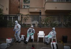 Firefighters wearing protective suits wait outside a nursing home before disinfecting it in efforts to prevent the spread of the new coronavirus in Barcelona, Spain, Monday, March 30, 2020. The new coronavirus causes mild or moderate symptoms for most people, but for some, especially older adults and people with existing health problems, it can cause more severe illness or death. (AP Photo/Felipe Dana)