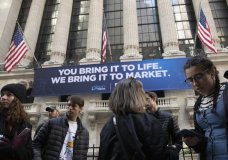FILE - In this Monday, March 9, 2020 file photo, people stop to look at the New York Stock Exchange. Stocks are opening sharply lower on Wall Street Wednesday as fears of economic fallout from the coronavirus outbreak grip markets again. (AP Photo/Mark Lennihan, File)