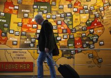 In this March 18, 2020 photo, a traveler checks his mobile telephone while passing a map of the United States on the way to the security checkpoint in the main terminal in Denver International Airport in Denver. Americans are increasingly worried they or a loved one will be infected by the coronavirus, with two-thirds now saying they're at least somewhat concerned — up from less than half who said so a month ago. That's according to a new poll from The Associated Press-NORC Center for Public Affairs Research that finds about 3 in 10 Americans say they're not worried at all. (AP Photo/David Zalubowski)