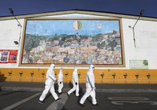 """Workers in protective body suits walk past sinks for hand washing at the """"Corabastos,"""" one of Latin America's largest food distribution centers, as they work to disinfect it to help contain the spread of the new coronavirus in Bogota, Colombia, Friday, April 10, 2020. (AP Photo/Fernando Vergara)"""