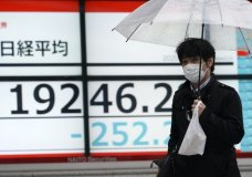 A man with a protective mask walks in the rain past an electronic stock board showing Japan's Nikkei 225 index at a securities firm in Tokyo Monday, April 13, 2020. Asian shares fell Monday amid absence of fresh news after U.S. markets were closed for Good Friday and European, Australian and Hong Kong trading continued to be closed for Easter holidays. (AP Photo/Eugene Hoshiko)