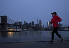 "ogger wearing a mask runs along Brooklyn Bridge Park, Tuesday night, April 14, 2020 during the coronavirus pandemic in New York. Known as ""The City That Never Sleeps,"" New York's streets are particularly empty during the pandemic. (AP Photo/Mark Lennihan)"