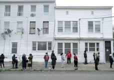 People wait in line for food assistance due to the coronavirus pandemic in Paterson, N.J., Wednesday, April 29, 2020. (AP Photo/Seth Wenig)