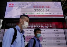 People wearing face masks walk past a bank electronic board showing the Hong Kong share index Tuesday, May 5, 2020. Shares advanced in Asia early Tuesday after Wall Street shook off a weak start and ended with modest gains thanks to another solid showing from big technology companies. (AP Photo/Vincent Yu)