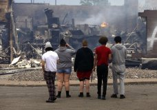 Onlookers watch as smoke smolders from a destroyed fast food restaurant near the Minneapolis Police Third Precinct, Thursday, May 28, 2020, after a night of rioting and looting as protests continue over the death of George Floyd, who died in police custody Monday night in Minneapolis after video shared online by a bystander showed a white officer kneeling on his neck during his arrest as he pleaded that he couldn't breathe. (AP Photo/Jim Mone)