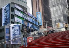 FILE - This March 20, 2020 file photo shows pedestrians in a sparsely populated Times Square in New York. COVID-19 has shaken theater fans and shuttered all New York City's venues, including Broadway, which grossed $1.8 billion last season and attracted a record 15 million people. How Broadway — one the city's jewels — will reopen is still not clear. (AP Photo/John Minchillo, File)
