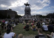 Protesters sit near the statue of Robert E. Lee on Monument Avenue in Richmond, Va., Wednesday, June 3, 2020. (Bob Brown/Richmond Times-Dispatch via AP)