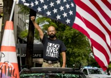 George Floyd's name is written on the windshield as John Coy wears a shirt that reads Black Lives Matter and stands through his sunroof with his fist in the air at 16th Street Northwest renamed Black Lives Matter Plaza near the White House, Friday, June 19, 2020, in Washington. (AP Photo/Andrew Harnik)