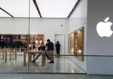 FILE - In this March 14 2020 file photo, Apple employees work inside a closed Apple store in Miami. Apple is temporarily closing 11 stores in Arizona, Florida, North Carolina and South Carolina just few weeks after reopening them in hopes that consumers would be able to shop in them without raising the risk of infecting them or company workers with the novel coronavirus that caused COVID-19. (AP Photo/Lynne Sladky, File)