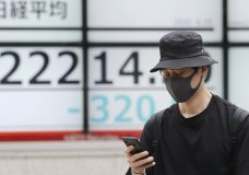 A man walks by an electronic stock board of a securities firm in Tokyo, Thursday, June 25, 2020. Shares declined in Asia on Thursday after a sharp retreat overnight on Wall Street as new coronavirus cases in the U.S. climbed to their highest level in two months, dimming investors' hopes for a relatively quick economic turnaround. (AP Photo/Koji Sasahara)