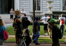 FILE - In this June 28, 2020 file photo, armed homeowners Mark and Patricia McCloskey confront protesters marching to St. Louis Mayor Lyda Krewson's house in the Central West End of St. Louis. On Friday, July 3, 2020, The Associated Press reported on stories circulating online incorrectly asserting the homeowners were aiming a handgun at an armed protester in front their mansion in St. Louis. The protester at right is holding a video camera and microphone, not a gun. (Laurie Skrivan/St. Louis Post-Dispatch via AP)