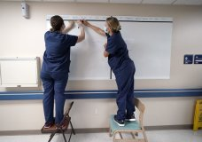 Registered nurses Army Capt. Rachel Curtis, right, and Capt. Christa Angelotti, with the Urban Augmentation Medical Task Force, sets up a patient board inside a wing at United Memorial Medical Center, Thursday, July 16, 2020, in Houston. Soldiers will treat COVID-19 patients in the newly setup hospital wing as Texas receives help from across the country to deal with its coronavirus surge. (AP Photo/David J. Phillip)