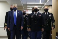 "FILE - In this July 11, 2020, file photo President Donald Trump, foreground left, wears a face mask as he walks with others down a hallway during a visit to Walter Reed National Military Medical Center in Bethesda, Md. On Tuesday, July 21, Trump professed a newfound respect for the protective face masks he has seldom worn. ""Whether you like the mask or not, they have an impact,"" he said. ""I'm getting used to the mask,"" he added, pulling one out after months of suggesting that mask-wearing was a political statement against him. (AP Photo/Patrick Semansky, File)"