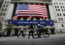 FILE - In this Tuesday, July 7, 2020 file photo, pedestrians wearing protective masks during the coronavirus pandemic pass by the New York Stock Exchange in New York. (AP Photo/Frank Franklin II, File)