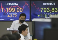 A currency trader talks with his colleague at the foreign exchange dealing room of the KEB Hana Bank headquarters in Seoul, South Korea, Thursday, July 23, 2020. Shares were mixed in Asia on Thursday, with the region's biggest market in Tokyo closed for a four-day weekend. (AP Photo/Ahn Young-joon)