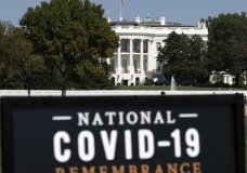 The White House is seen in the background as sign of the National COVID-19 Remembrance, event at The Ellipse outside of the White House, Sunday, Oct. 4, 2020, in Washington. More Americans blame the U.S. government than foreign powers for the coronavirus crisis in United States, rejecting the Trump administration's contention that China is most at fault for the spread of the disease. That's according to a new poll by The University of Chicago Harris School of Public Policy and The Associated Press-NORC Center for Public Affairs Research.(AP Photo/Jose Luis Magana)