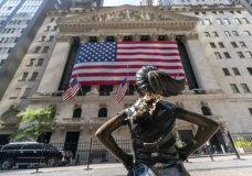 """FILE - In this Monday, Sept. 21, 2020 file photo, the """"Fearless Girl"""" bronze sculpture looks towards the New York Stock Exchange. Stocks are falling early Friday, Oct. 2 as Wall Street's first reaction to President Donald Trump's testing positive for the coronavirus was to retrench. The S&P 500 was 0.9% lower after the first few minutes of trading, dropping with stocks around the world, Treasury yields and oil as investors pulled out of riskier investments and into safer ones. (AP Photo/Mary Altaffer)"""