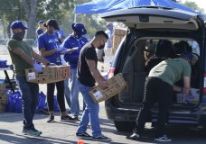 Volunteers help distribute some 1,500 Thanksgiving meals, including an assortment of dinner fixings at a drive-thru to not-for-profit community organizations at Dodger Stadium parking lot in Los Angeles Thursday, Nov. 19, 2020. Los Angeles Dodgers, the Los Angeles Dodgers Foundation (LADF), and team partner Smart & Final host the 16th annual Community Thanksgiving Turkey Giveaway. (AP Photo/Damian Dovarganes)