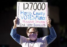 Demonstrator Gina Dusterhoft holds up a sign as she walks to join others standing across the street from the federal courthouse in Houston, Monday, Nov. 2, 2020, before a hearing in federal court involving drive-thru ballots cast in Harris County. The lawsuit was brought by conservative Texas activists, who have railed against expanded voting access in Harris County, in an effort to invalidate nearly 127,000 votes in Houston because the ballots were cast at drive-thru polling centers established during the pandemic. (AP Photo/David J. Phillip)