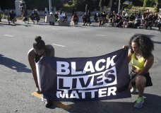 FILE - In this July 11, 2020 file photo, Alycia Pascual-Pena, left, and Marley Ralph kneel while holding a Black Lives Matter banner during a protest in memory of Breonna Taylor, in Los Angeles. Taylor was killed in her apartment by members of the Louisville, Ky., Metro Police Department on March 13. The International Law Enforcement Educators and Trainers Association, a prominent law enforcement training group, is promoting a lengthy research document riddled with falsehoods and conspiracies that urges local police to treat Black Lives Matter activists as terrorists plotting a violent revolution. The document contains misinformation and inflammatory rhetoric that could incite officers against protesters and people of color, critics said. (AP Photo/Marcio Jose Sanchez, File)