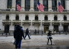 FILE - Pedestrians pass the New York Stock Exchange Tuesday, Feb. 16, 2021, in New York. Stocks are off to a mostly higher start, Friday, Feb. 26, as technology companies find their footing after a big sell-off a day earlier. (AP Photo/Frank Franklin II, File)