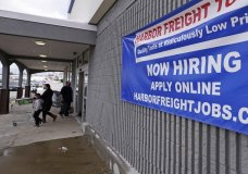 "FILE - In this Dec. 10, 2020 file photo, a ""Now Hiring"" sign hangs on the front wall of a Harbor Freight Tools store in Manchester, N.H. U.S. employers cut back sharply on hiring in December, particularly in pandemic-hit industries such as restaurants and hotels, as soaring virus infections and government restrictions weakened the economy that month. The number of available jobs rose slightly and layoffs fell, according to the Labor Department's Tuesday report, known as the Job Openings and Labor Turnover Survey, or JOLTS. (AP Photo/Charles Krupa, File)"