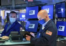 In this photo provided by the New York Stock Exchange, trader Fred DeMarco, right, works on the floor, Thursday April 22, 2021. Stocks wobbled between small gains and losses Thursday as investors continue to focus on company earnings reports and the economic recovery. (Courtney Crow/New York Stock Exchange via AP)