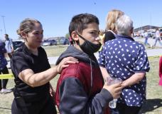 RETRANSMISSION TO CORRECT FIRST NAME TO ADELA - Adela Rodriguez, left, walks with her son, Yandel Rodriguez, 12, at the high school where people were evacuated after a shooting at the nearby Rigby Middle School earlier Thursday, May 6, 2021, in Rigby, Idaho. Authorities said that two students and a custodian were injured, and a male student has been taken into custody. (AP Photo/Natalie Behring)