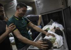 A Palestinian relative mourns over the bodies of four young brothers from the Al-tanani family who were found under the rubble of a destroyed house following Israeli airstrikes in Beit Lahiya, northern Gaza Strip, Friday, May 14, 2021. (AP Photo/Khalil Hamra)