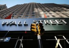A sign for a Wall Street building is shown, Wednesday, May 19, 2021 in New York. Stocks are opening broadly higher on Wall Street, starting the week on a positive note following two straight weeks of losses for most major indexes. The S&P 500 was up 0.6% in the early going Monday, May 24. (AP Photo/Mark Lennihan)